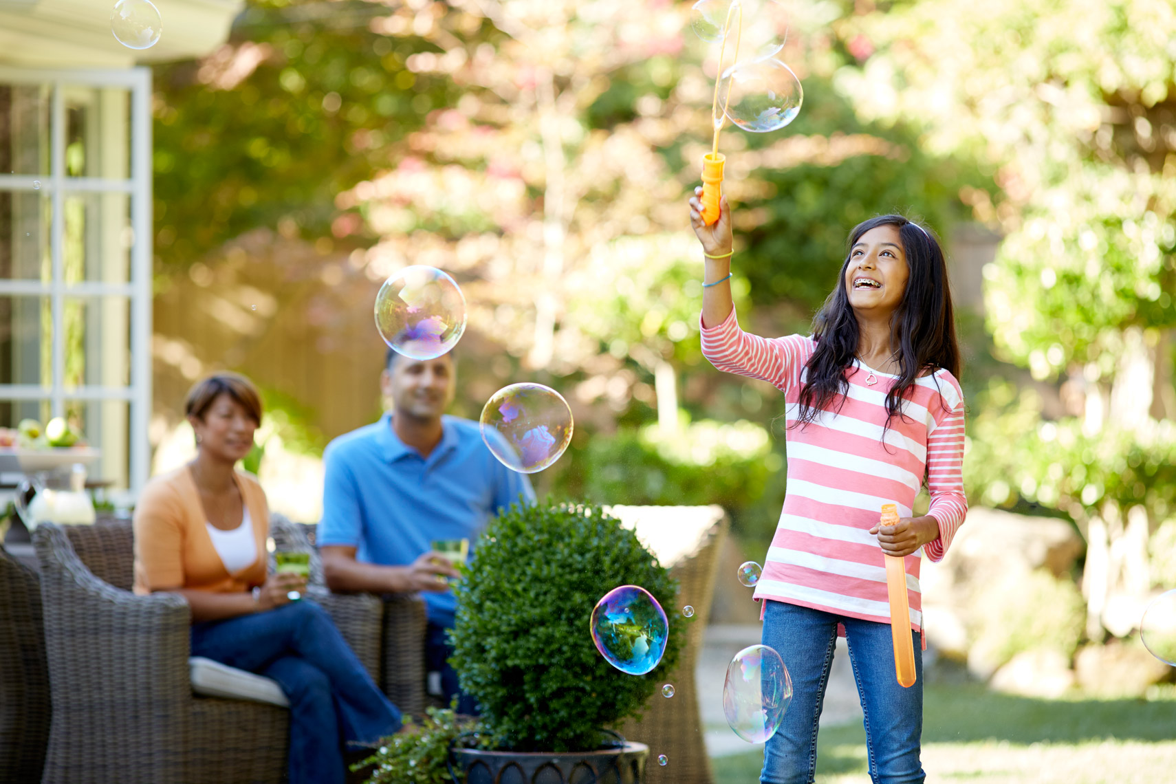 lifestyle photographer, advertising photographer, girl blowing bubbles, garden, yard, parents and kids, lawn, garden, green space, backyard, san francisco