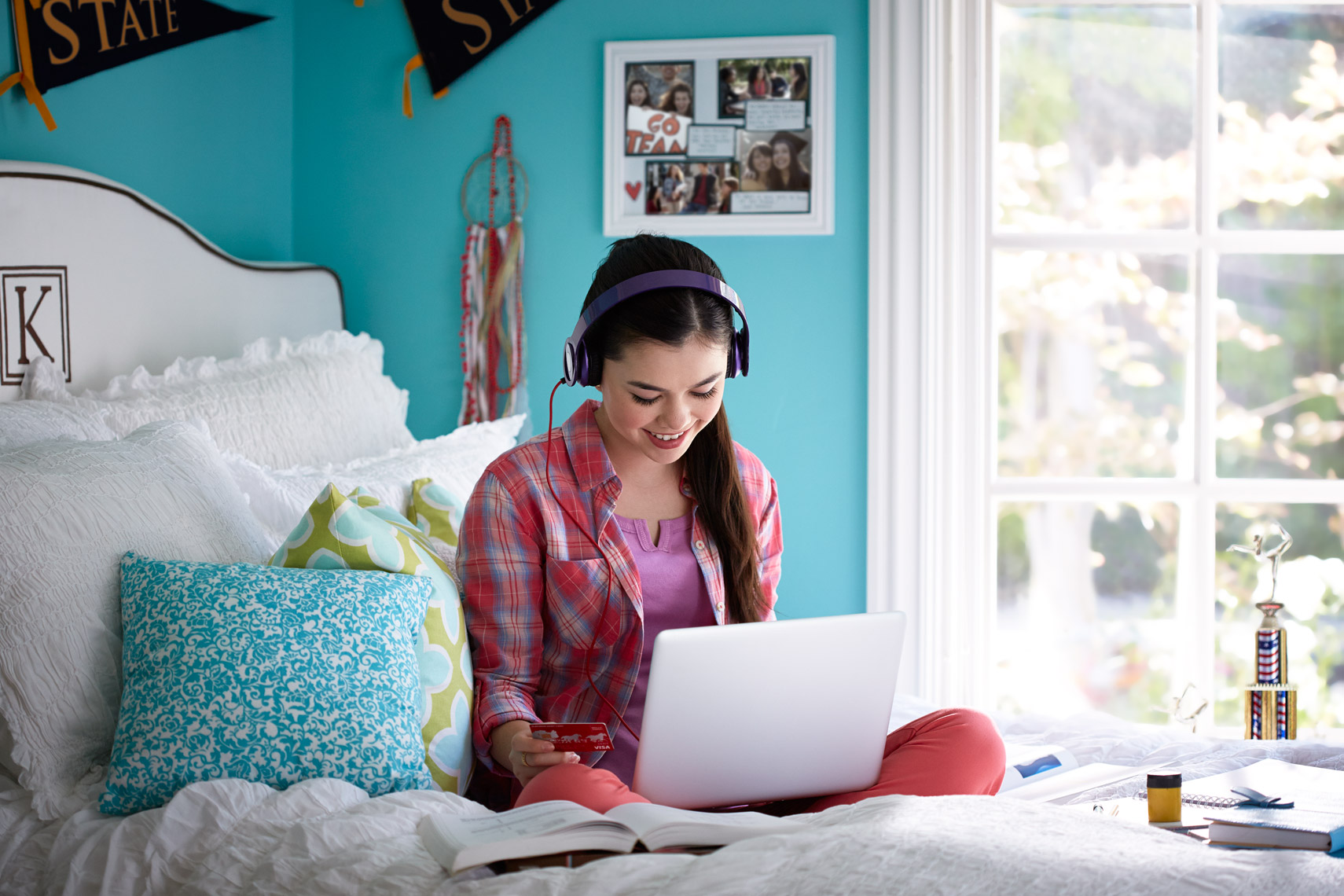 lifestyle photographer, advertising photographer, teenager in room, girl with headphone, listening to music, blue room, bedroom, girl in bed with laptop computer