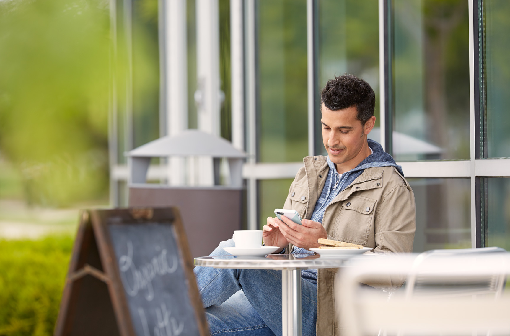 young man sitting at outdoor cafe drinking coffee in the city, lifestyle, advertising, commercial photography