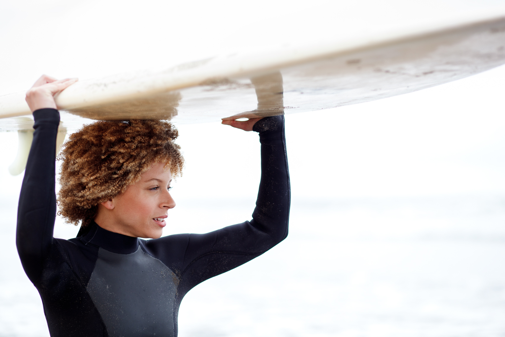 lifestyle photographer, advertising photographer, girl surfer on the beach, surfboard, african american, woman in wetsuit, female