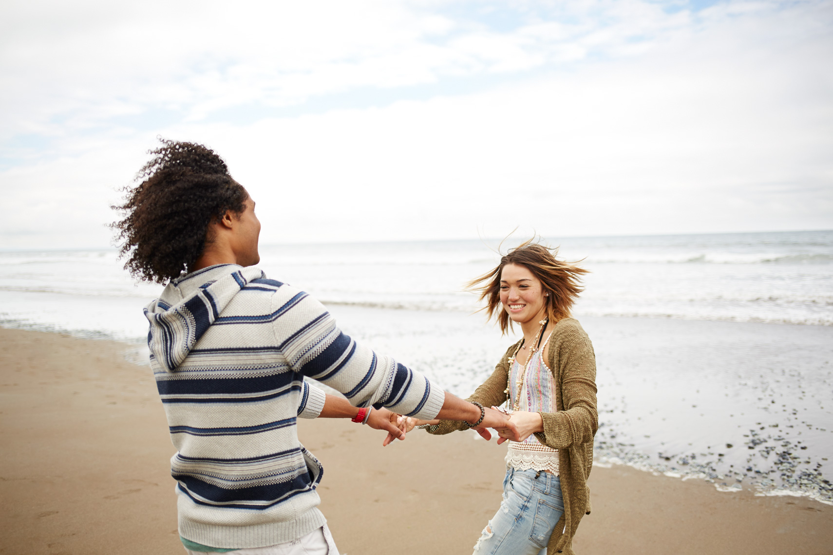couples on the beach facing the ocean hugging, african american man, blonde white woman, stinson beach, lifestyle photography, commercial photography, advertising photography, san francisco, holding hands