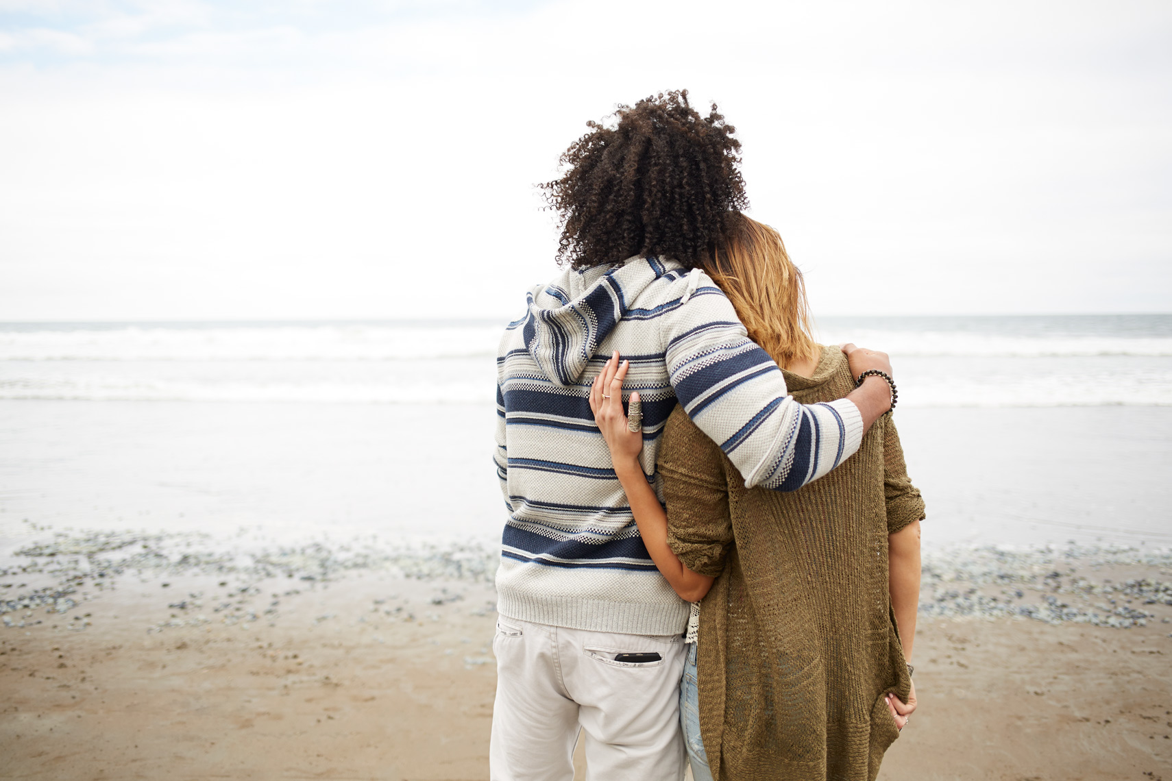 couple on the beach facing the ocean hugging, african american man, blonde white woman, stinson beach, lifestyle photography, commercial photography, advertising photography, san francisco