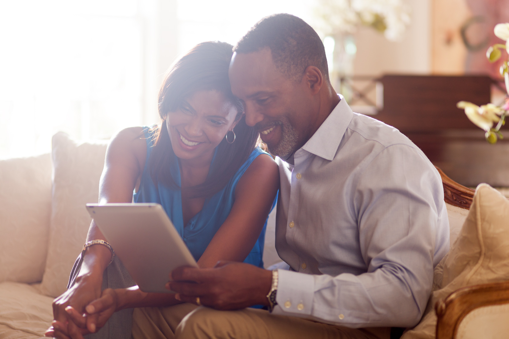 San Francisco Bay Area Advertising, Lifestyle, Commercial Photographer, african american black couple sitting on the couch sofa in the living room with ipad smiling discussing at home