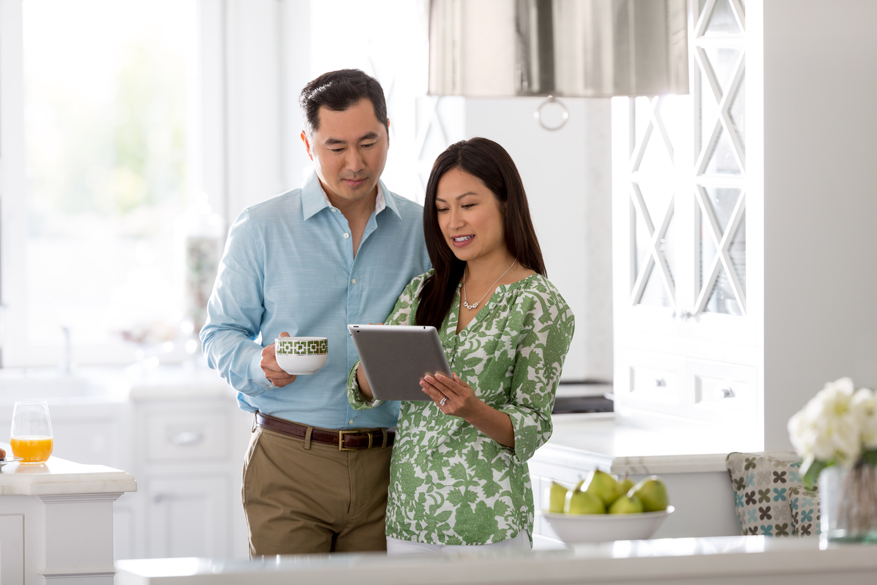 San Francisco Bay Area Advertising, Lifestyle, Commercial Photographer, young asian couple in the kitchen with ipad discussing with white background