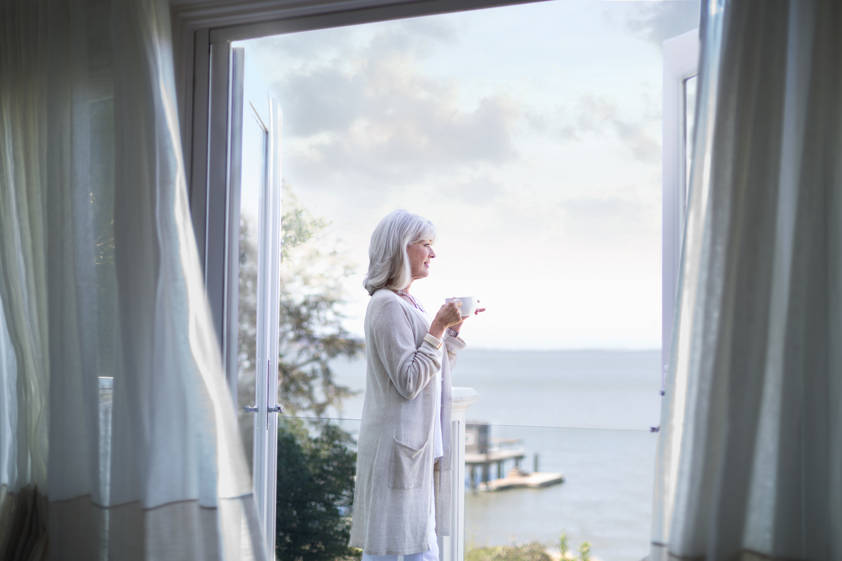 San Francisco Bay Area Advertising, Lifestyle, Commercial Photographer, older woman with gray hair looking out of the window to see the ocean beach with a cup of coffee