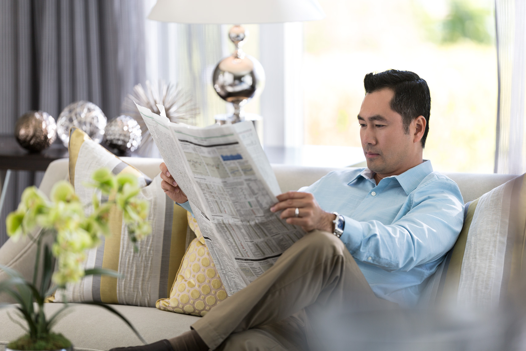 San Francisco Bay Area Advertising, Lifestyle, Commercial Photographer, asian man in the living room on a sofa couch reading newspaper at home