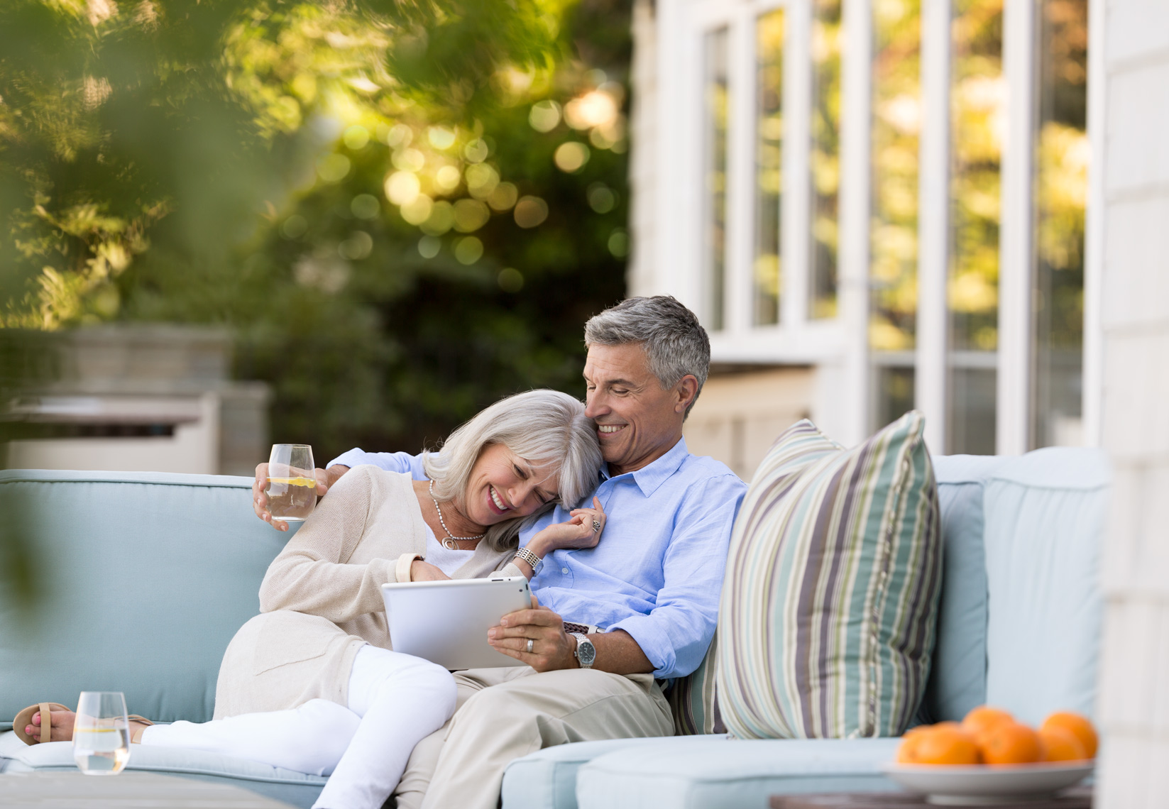 San Francisco Bay Area Advertising, Lifestyle, Commercial Photographer, older couple with gray hair sitting outdoor backyard on the patio sofa embracing and laughing