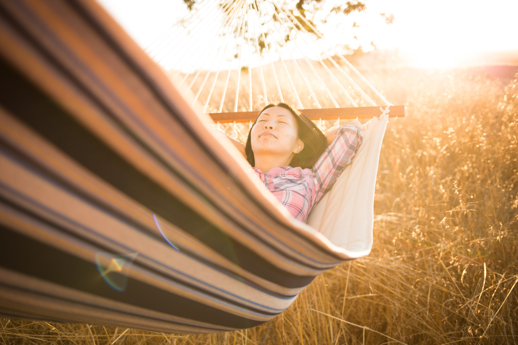 San Francisco Bay Area Advertising, Lifestyle, Commercial Photographer, asian female laying on a hammock outdoor in the grass sunset, summer, swinging, afternoon