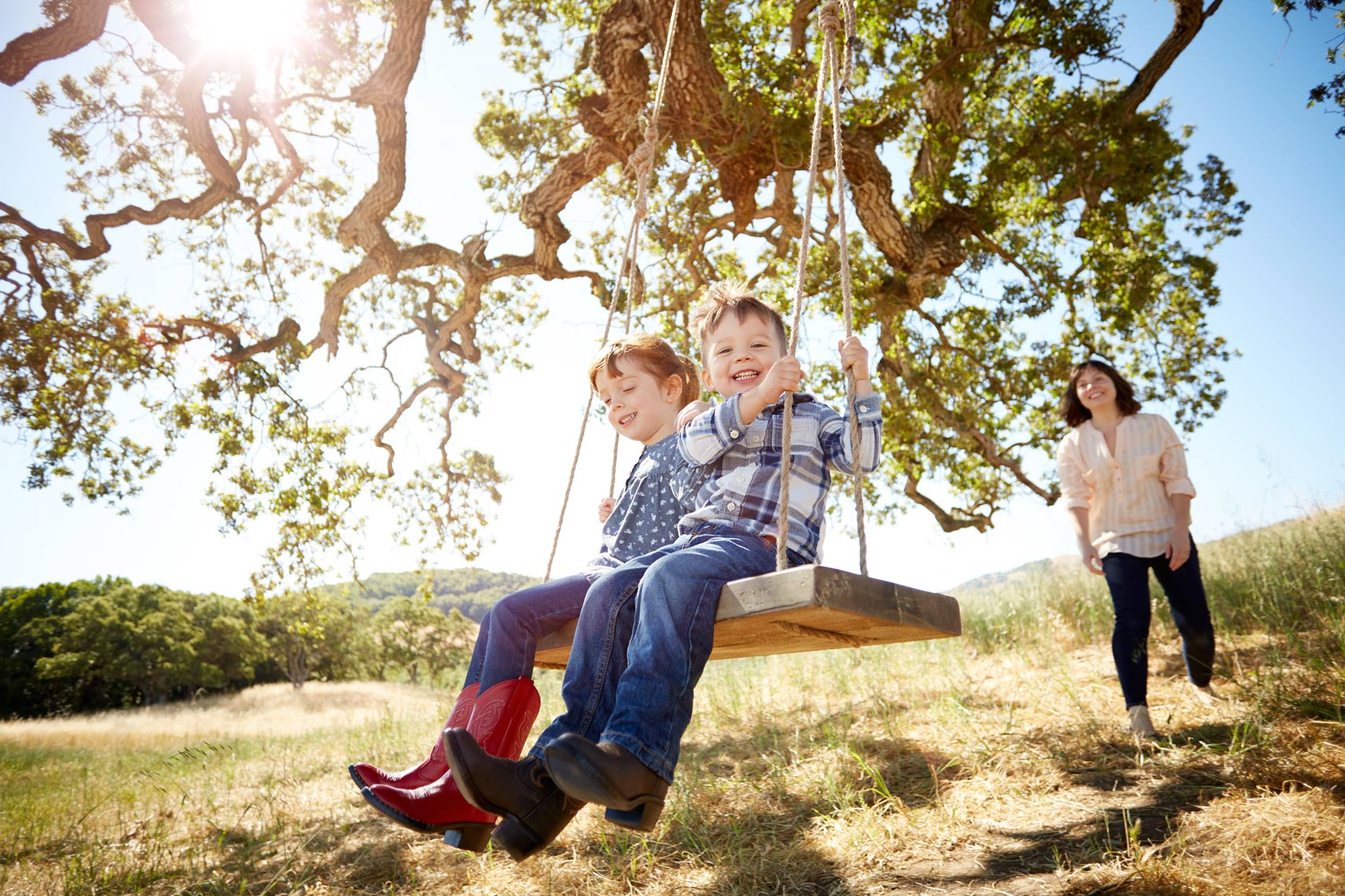 lifestyle photographer, advertising photographer, kids playing, kids on the swing, oak tree, outdoor playground, girl and boy, kids in cowboy boots